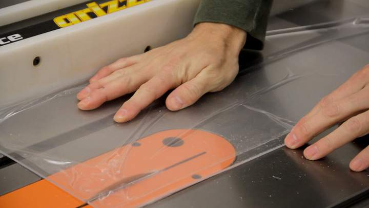 A sheet of clear acrylic is cut on a table saw.