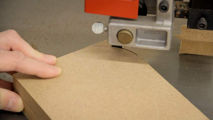A curve is cut in a piece of MDF using a band saw.