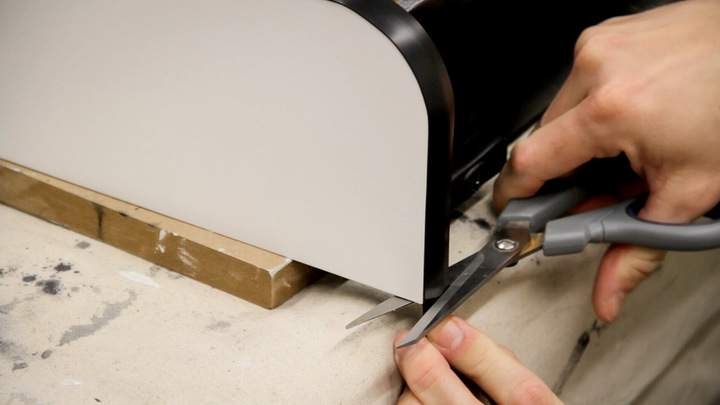 Plastic T-Molding is cut to length with a pair of scissors.