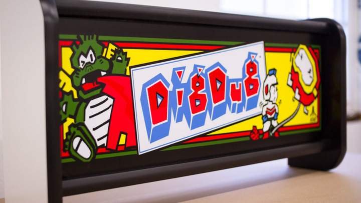 A lit Dig Dug arcade marquee in the dark.