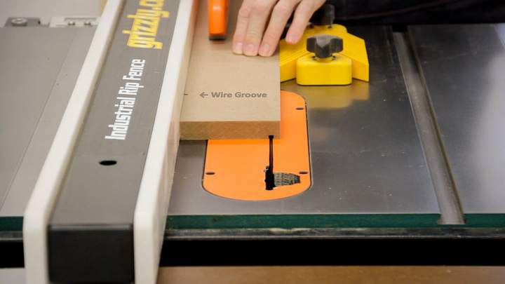A bevel is cut in a piece of MDF on a table saw.