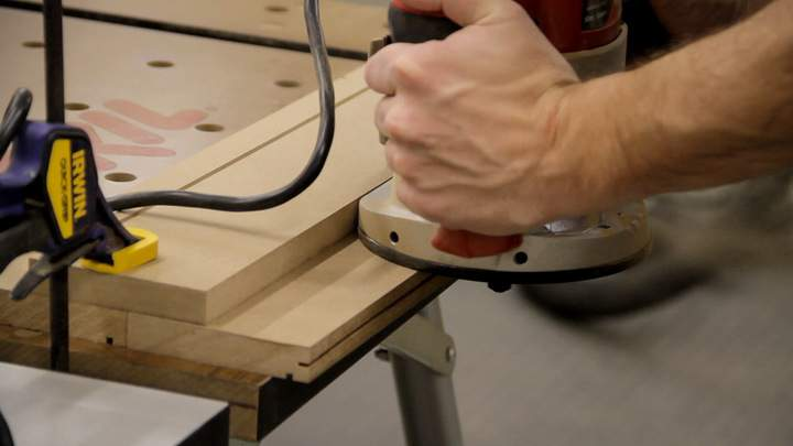 A slot is cut along a MDF edge using a router.
