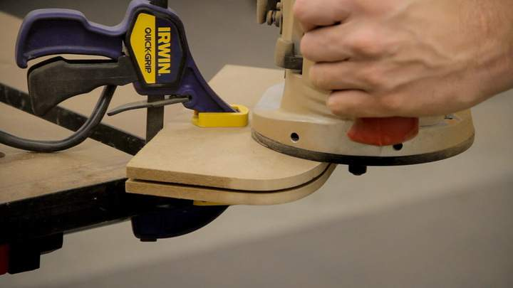 A slot is cut along a curved MDF edge using a router.