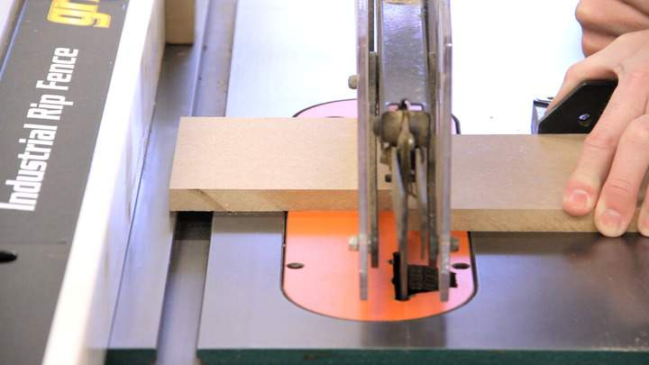 A table saw is used to cut a small sheet of MDF.