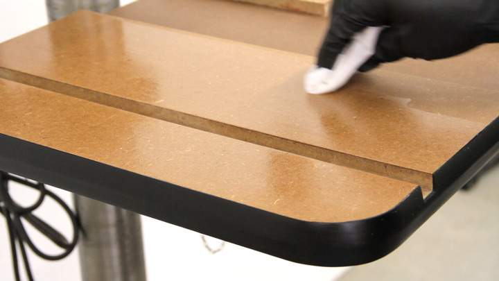 Wipe-on polyurethane is applied to the table top.