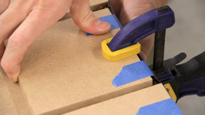 Tape is applied to secure plastic T-molding in place.