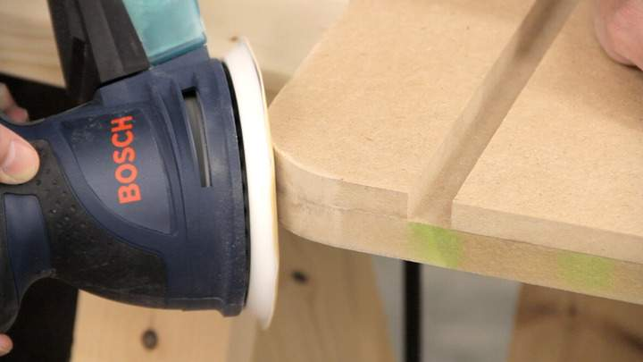 A random orbit sander is used to smooth the cut corner.