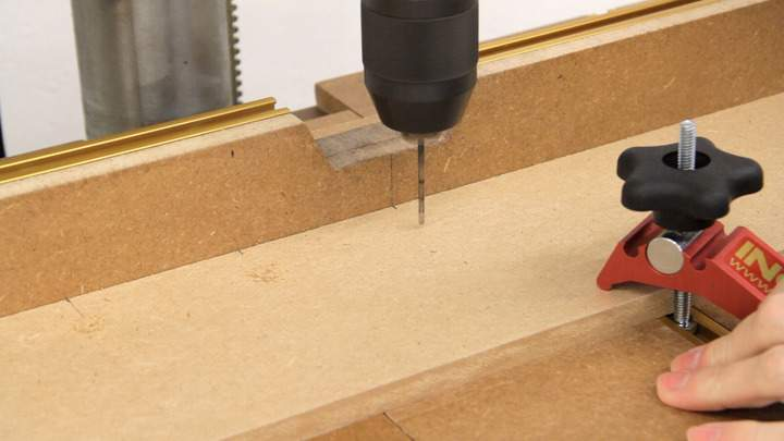 A drill press is used to drill several small holes in a piece of MDF.