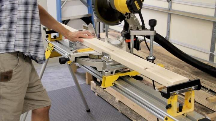 A 2x4 is cut using a power miter saw.