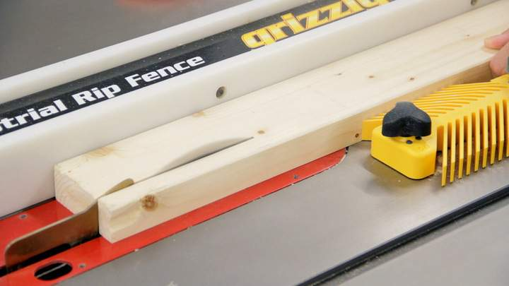 A table saw is used to rip a 2x4.