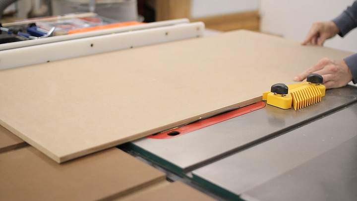 A table saw is used to cut a bevel down a piece of MDF.