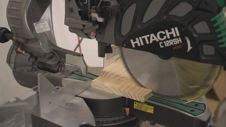A miter saw is used to cut a pine board.
