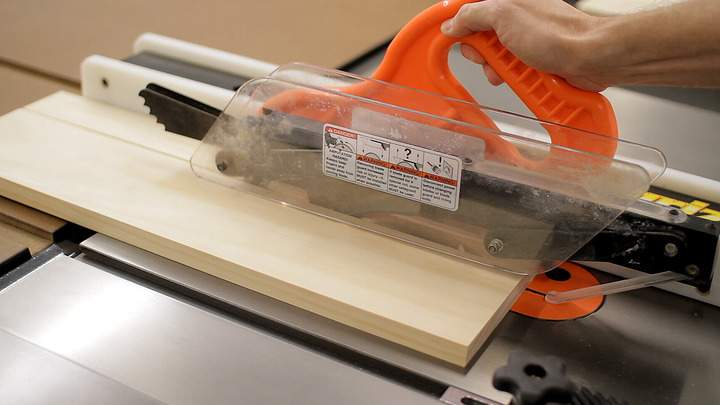A table saw is used to rip a pine board to width.
