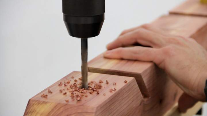A drill press is used to drill a hole in a cedar skateboard rack.