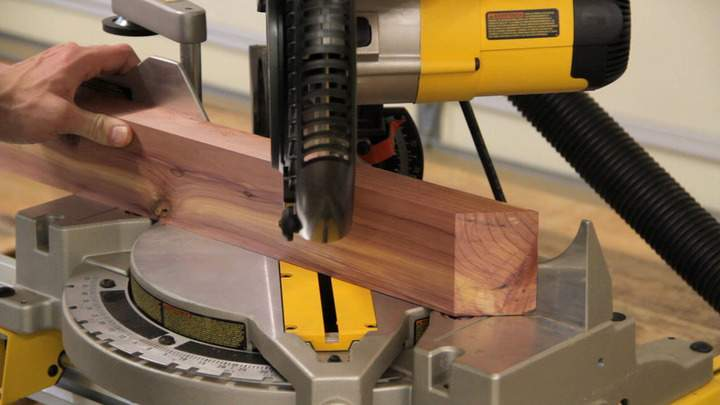 A miter saw is used to cut a cedar board into separate parts.