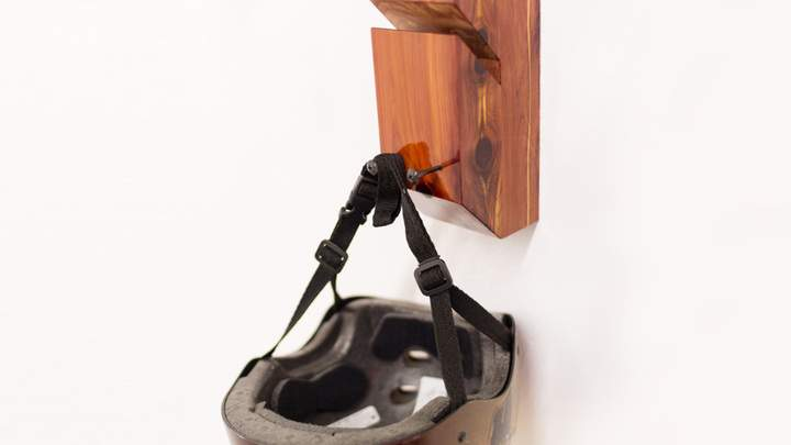 A helmet hanging from a cedar skateboard rack.