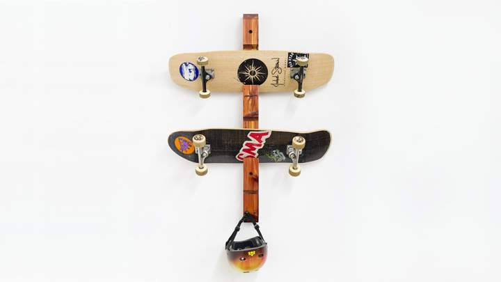 A wooden skateboard rack, skateboards, and helmet.