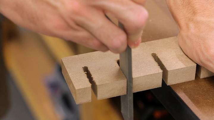 A file is used to clean the edge of a slot in MDF.