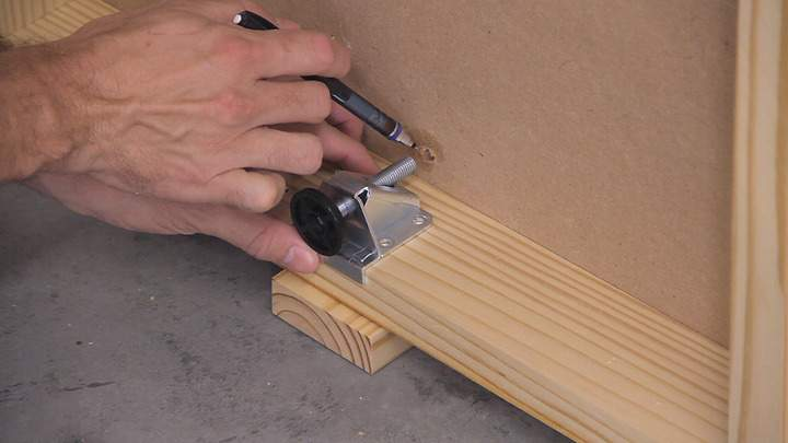 A pencil is used to point to an access hole in an MDF shelf.