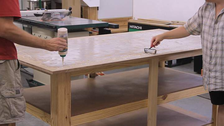 Glue is spread with a roller on an MDF table top.