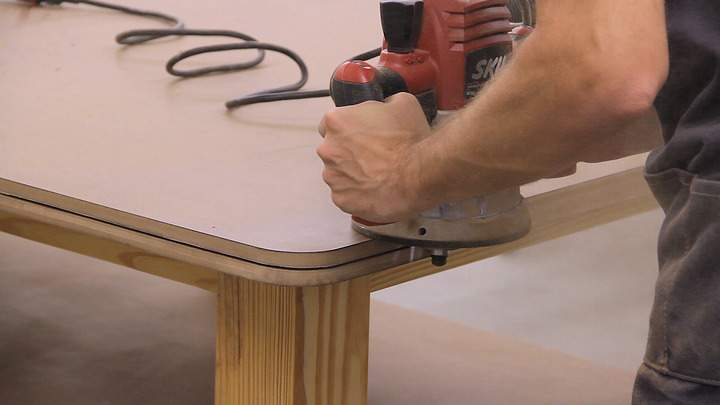 A router is used to cut a slot on the edge of a workbench top.