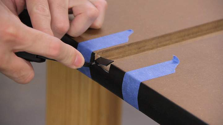 A knife is used to cut a notch in a piece of T-molding.