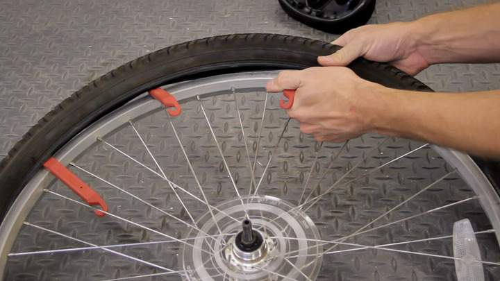 Using multiple tire levers to remove a tire from a bicycle wheel.