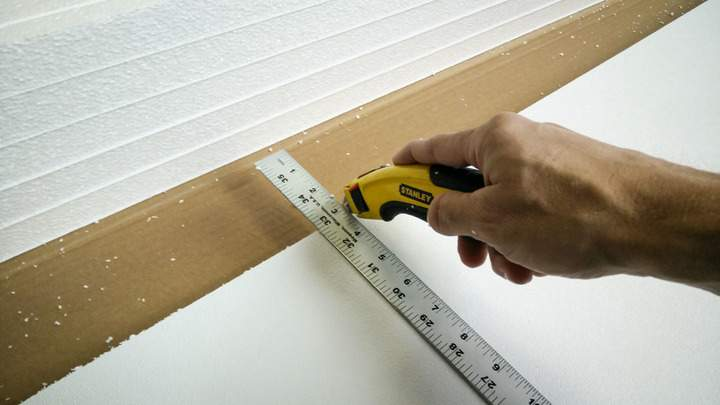 Scoring a piece of garage door insulation with a knife