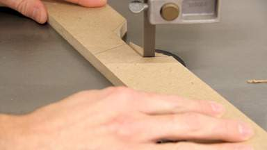 A band saw is used to cut a notch in a piece of MDF.