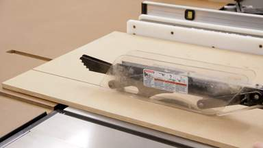A table saw is used to cut a large sheet of MDF.