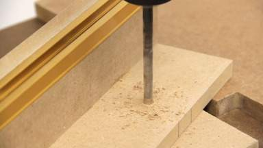 A hole is drilled in the MDF fence.