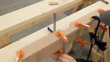 Glue and clamps are used to join two pieces of MDF.
