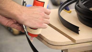 Glue is applied to plastic T-molding.