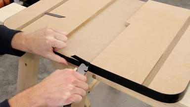 A knife is used to trim off excess plastic T-molding.
