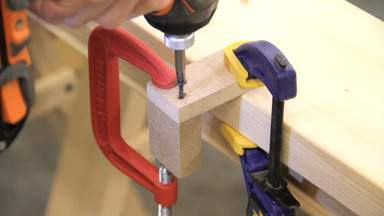 A drill is used to screw two small pieces of MDF together in an L shape.
