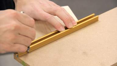 A pencil is used to mark a line on a piece of MDF.