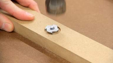 A T-nut is hammered into a piece of MDF.