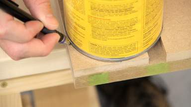 A can is used to trace a curve on the table top.