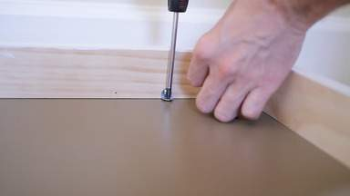 A screwdriver is used to attach the frame to the shelf top.