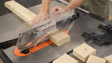 A table saw is used to cut a 2x4 into small blocks.