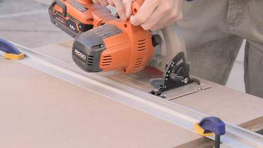 A circular saw is used to cut a large sheet of MDF.