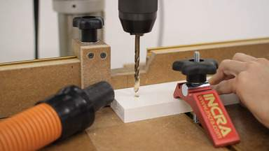 A drill press is used to drill holes in a wooden leg.