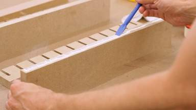 Glue is applied to the edge of a piece of MDF.