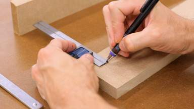A pencil and square are used to mark on a piece of MDF.