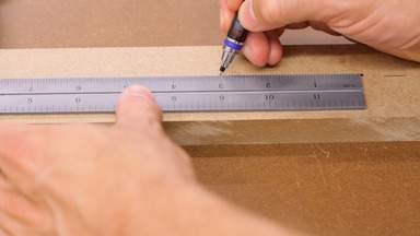 A pencil and ruler are used to mark on a piece of MDF.
