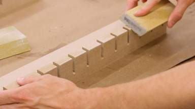A sanding pad is used on the front edge of the rack.