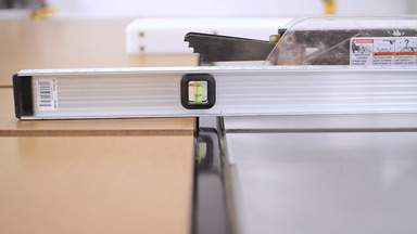 A level is used to adjust the workbench top to match the table saw top.