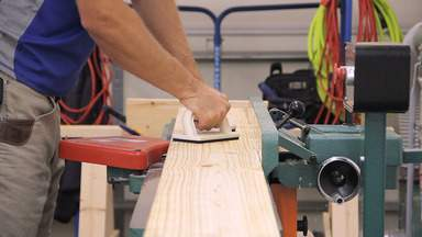 A jointer is used to flatten the face of a piece of lumber.