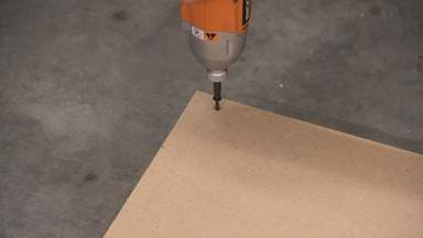 A drill is used to insert a screw into a piece of MDF.