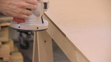 A router is used to trim the edge of a piece of MDF.